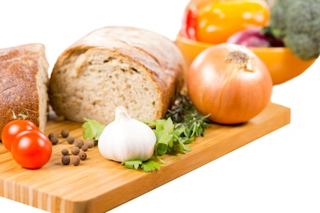 Preparing a savoury vegetarian meal with a fresh garlic, rosemary and parsley, cherry tomatoes, onion and bread on a wooden chopping board with a bowl of mixed vegetables in the background Stock Photo - 18572643