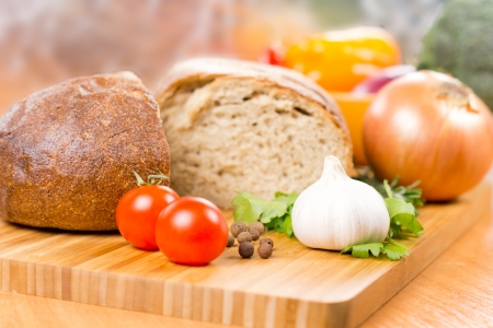 Preparing a meal with fresh whole garlic, tomato and parsley on a chopping board on a kitchen table with a loaf of bread and onion behind with shallow dof Stock Photo - 18572648