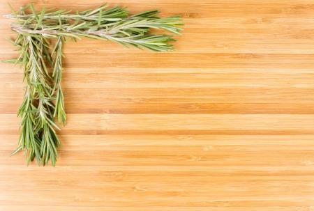 pungent: Rametti di rosmarino fresco per l'uso come un aromatico pungente condimento in cucina organizzato come un angolo su uno sfondo di legno