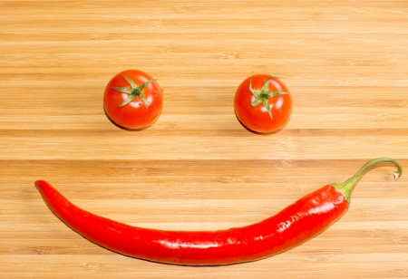 Happy face made of two tomatoes and a chili pepper, on wooden background, high angle Stock Photo - 18572653