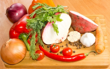 A selection of colourful farm fresh organic vegetables, herbs and spices on a wooden chopping board to be used as ingredients in cooking Stock Photo - 18572656