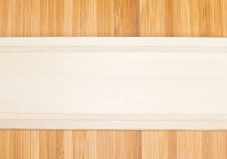 definite: Natural light wood banner formed from the partial view of a wooden kitchen utensil place horizantally over darker wood with a definite woodgrain pattern Stock Photo