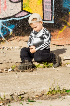introvert: Introvert lonely little boy sitting on the ground in front of a graffiti covered wall thinking in the sunshine with a moody expression