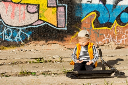 Little boy sitting with his scooter on the sidewalk in front of a colourful graffiti painted wall playing in the sunshine with copyspace photo