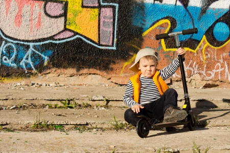 Adorable young boy sitting on the ground with his scooter held upright in his hand posing in front of a wall covered in colourful bold graffiti photo