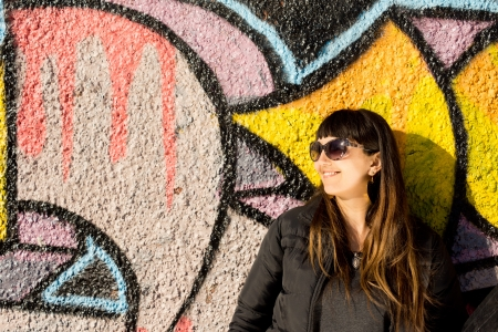 Laughing woman in sunglasses standing in the sunshine posing against a wall painted with colourful graffiti in bold geometric designs photo