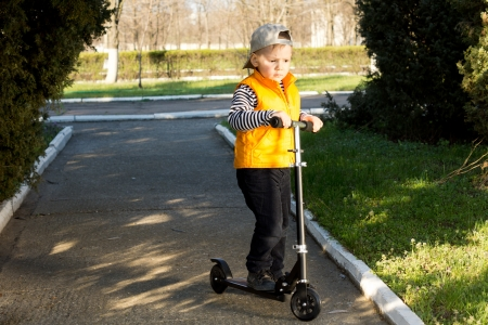 high visibility: Young boy riding a scooter up a paved outdoor pathway in a rural environment wearing a bright orange high visibility jacket and reversed baseball cap