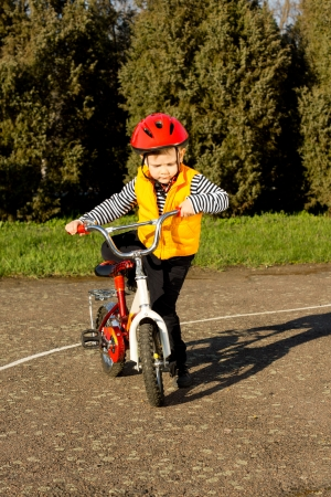 high visibility: Little boy wearing a safety helmet and high visibility jacket mounting his bicycle throwing his leg over the saddle as he prepares to go out for an enjoyable ride in the evening sunlight