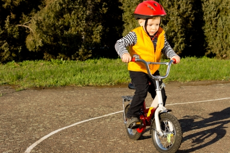 Cute young boy dressed in a colourful red safety helmet and orange high visibility jacket practising riding his bike on a quiet country lane