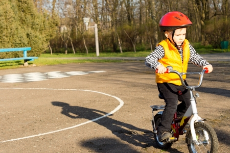 Cute little boy dressed in a safety helmet and high visibility jacket pedalling his bike on a quiet country road photo