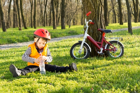 Cute young boy out riding on his bicycle stopping for a drink of bottled water sitting on lush green grass in a wooded park with his bike leaning up against a tree nearby