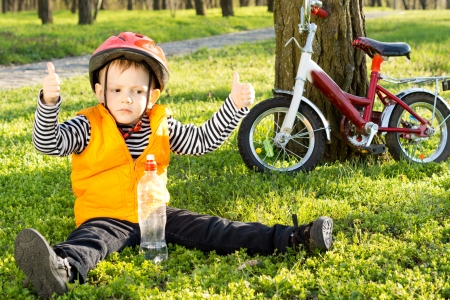 Small boy out riding his bicycle in the park giving a thumbs up of approval as he sits in his safety gear on green grass drinking water from a plastic bottle Reklamní fotografie