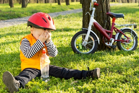 embarassed: Embarassed little boy in a safety helmet hiding his face from the photographer while sitting on lush green grass drinking bottled water with his bicycle propped up against a tree alongside him