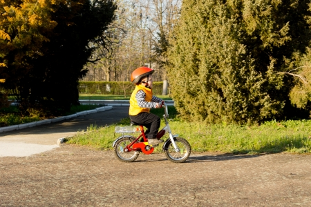 Cute little boy learning to ride pedalling his bicycle along a rural country lane dressed in his safety helmet and bright orange high visibility jacket Stock Photo