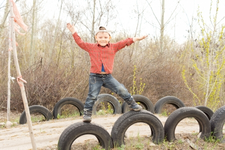 playground ride: Cute little boy balanced on old tyres inserted into the ground on either side of a rural lane with his arms outspread and a happy smile on his face