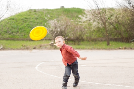 Cute attractive little boy playing outdoors in a park with a brightly coloured plastic yellow frisbee throwing it through the air photo