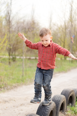 Small boy balancing on old tyres which have been sunk into the ground to form a safety barrier at the side of a rural lane in the countryside photo