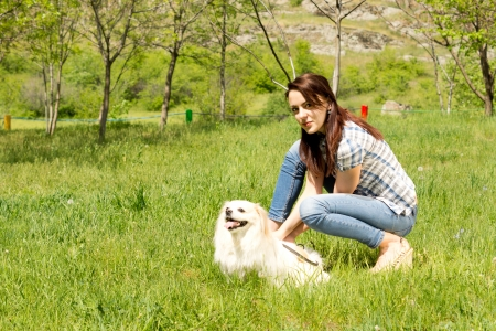 crouched: Pretty casual young woman in jeans bending down and playing with her cute little long haired dog in green grass in the countryside
