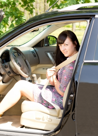 Young attractive brunette putting on her safety belt while seated in a car. photo