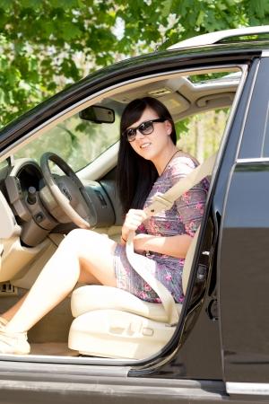 cinturon seguridad: Joven y atractiva mujer morena con gafas de sol que pone en su cintur�n de seguridad mientras se est� sentado en un coche. Foto de archivo