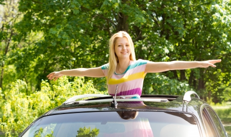 Image of a gorgeous young female spreading her hands like a bird outside a moving car  photo