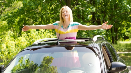 vivacious: Playful vivacious young blond woman standing in a car sunroof with her arms outstretched laughing happily in the sunshine Stock Photo