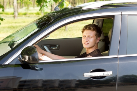 View through the open side window of a smiling handsome young man driving a car in countryside