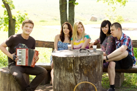 坐在树的树荫下的年轻人演奏手风琴的一个小组他的朋友当他们享受一天