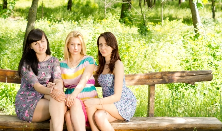 Three attractive young girls in stylish summer dresses sitting close together on a wooden bench in a lush green park photo