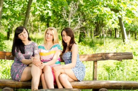 Three beautiful young female friends wearing trendy miniskirts sitting together on a wooden bench in lush green countryside photo