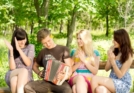 concertina: Three beautiful young female friends enjoying music played on a concertina accordion by a handsome young man as they clap to the rythm