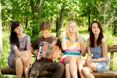 Young man seated in the shade of tree on a rustic wooden bench playing music for his three attractive women friends photo