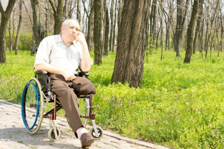 Pensive elderly amputee sitting alone on a rural pathway in his wheelchair with his chin resting on his hand staring into the distance