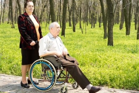 Elderly woman walking her husband, who has had one leg amputated above the knee, in his wheelchair along a rural path in woodland photo