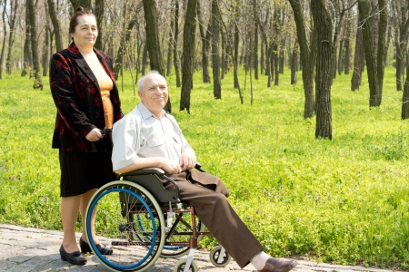 coping: Smiling elderly man with one leg amputated sitting in his wheelchair in a wooded park attended by his wife or carer Stock Photo