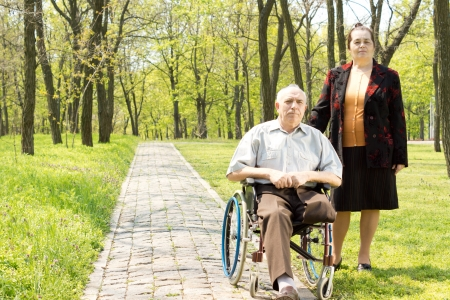 amputated: Handicapped elderly man with one leg amputated above the knee sitting in his wheelchair in a wooded park with his wife standing at his side