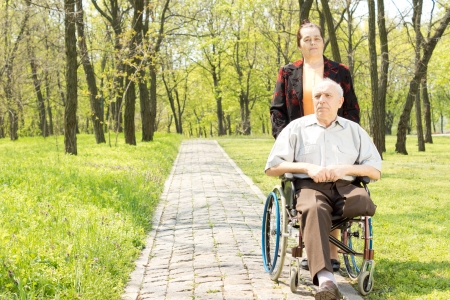 Wife walking a disabled man in a wheelchair who has had one leg amputated through a peaceful rural wooded park Stock Photo