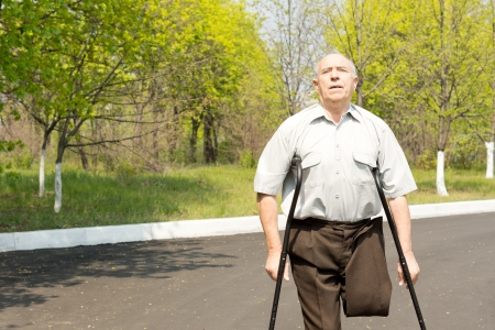 gerontology: Elderly male amputee balanced on crutches in a rural street with his trousers pinned up to reveal his stump
