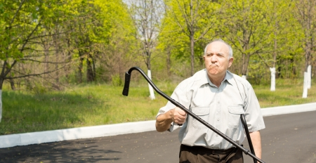 gerontology: Elderly man standing in a rural street bordered by woodland waving his crutch in the air Stock Photo