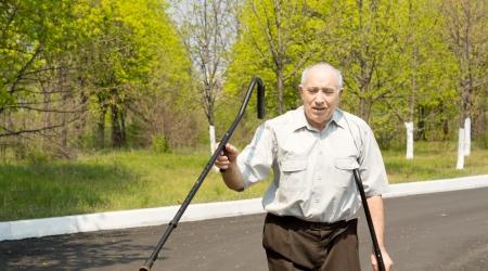 gerontology: Senior man walking on crutches down a rural lane waving one crutch in the air Stock Photo