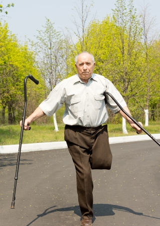 gerontology: Elderly disabled man who has undergone an above the knee amputation on one leg standing in a rural road balancing on the other leg and waving his crutches in the air Stock Photo