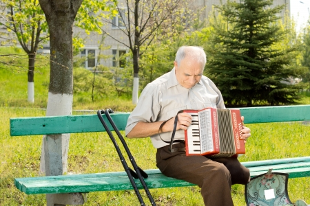 amputated: Handicapped senior man with one leg amputated above the knee sitting on a park bench playing the accordion Stock Photo