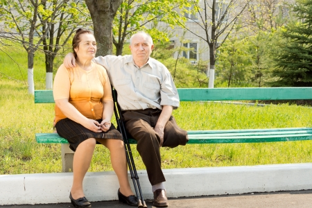 Elderly couple sitting close together on a park bench enjoying the sunshine - the husband has one leg amputated and is using crutches