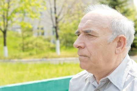 Serious thoughtful senior man sitting sideways to the camera staring into the distance, head and shoulders portrait in a rural park