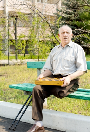 Portrait of an old man sitting on the bench park and holding chess board photo