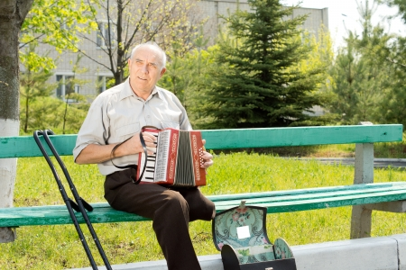 Disabled senior man with one leg amputated above the knee sitting on a park bench playing the accordion photo