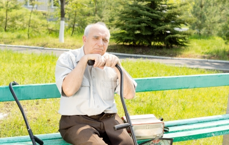 Portrait of senior man sitting on the bench park waiting for someone photo