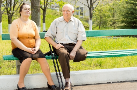 Portrait of couple talking and sitting on the park bench photo