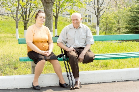 Portrait of senior man and mid age woman sitting on bench in the park photo