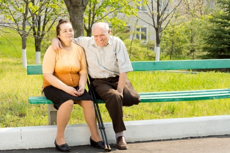Happy couple sitting on bench and talking in the park photo